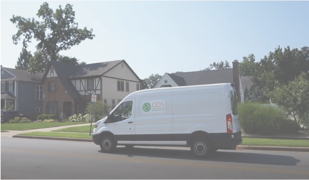 "a white van with a ""GDS"" sign on the side on the street in front of three houses"
